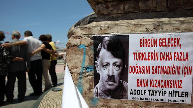 """A depiction of Turkish Prime Minister Recep Tayyip Erdogan portraying him as Nazi leader Adolf Hitler is pasted on the front of Mustafa Kemal Ataturk's statue, founder of Turkey, at the Taksim square in Istanbul on Thursday, June 6, 2013. The sign reads ''One day you are going to be married me because I haven't sold much Turkish nature.'' In the first days of the protests last week, Erdogan dismissed the demonstrators as """"capulcu"""" - a Turkish word which translates as marauder, looter or plunderer. Protesters quickly turned the word to their advantage. They made it their own, Anglicizing it and turning it into a brand new verb, """"Capulling"""" - which means protesting, resisting the tear gas and shouting anti-Erdogan slogans. (AP Photo/Thanassis Stavrakis)"""