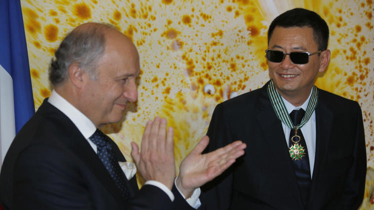 Hong Kong director Wong Kar-wai, right,  smiles as he receives the Commandeur des Arts et Lettres from French Foreign Minister Laurent Fabius, in Hong Kong Sunday, May 5, 2013. Wong has been given France's highest cultural honor. (AP Photo/Vincent Yu)