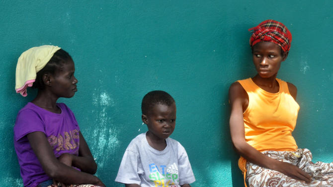 In this photo taken on Friday, Oct. 24, 2014, three people suspected of having contracted the Ebola virus await treatment outside a hospital inthe Bomi County area, near Monrovia, Liberia. More than 10,000 people have been infected with Ebola, according to figures released Saturday by the World Health Organization, as the outbreak continues to spread. Of those cases, 4,922 people have died. (AP Photo/Abbas Dulleh)