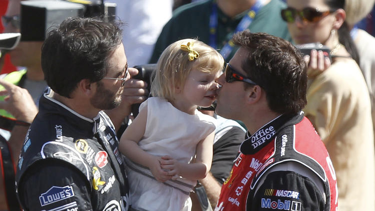 Jimmie Johnson, left, holds his daughter Genevieve, center, up as she gives a kiss to Tony Stewart before the NASCAR Sprint Cup Series auto race at Phoenix International Raceway on Sunday, March 4, 2012, in Avondale, Ariz. (AP Photo/Paul Connors)