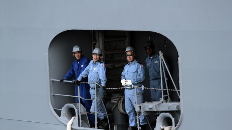 In this picture taken Friday, Sept. 21, 2012, Japanese sailors look out from their naval ship toward the British Royal Navy's nearby HMS Atherstone in the Persian Gulf. More than 30 nations are participating in an exercise responding to simulated sea-mine attacks in international waters _ a demonstration of international resolve to ensure maritime security in the strategic but volatile region. (AP Photo/Hasan Jamali)