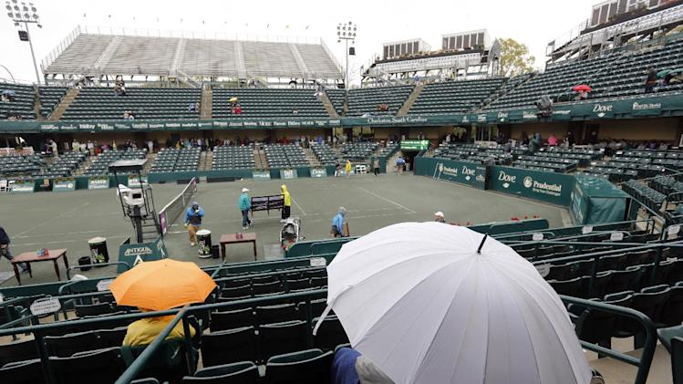 A few brave fans wait for the Bethanie Mattek-Sands vs. Madison Keys tennis match to begin during a weather delay at the Family Circle Cup tennis tournament in Charleston, S.C., Thursday, April 4, 2013.  (AP Photo/Mic Smith)