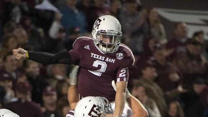 Texas A&M quarterback Johnny Manziel (2) gets a lift from Luke Joeckel (76) after running 18-yards for a touchdown during the third quarter of an NCAA college football game against Missouri, Saturday, Nov. 24, 2012, in College Station, Texas. (AP Photo/Dave Einsel)