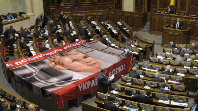 """A banner placed on seats usually by occupied by opposition lawmakers is used to protest against the arrest of Ukraine's former Prime Minister Yulia Tymoshenko, during a session in Kiev, Ukraine, Wednesday, Nov. 16, 2011. Tymoshenko, 50, was sentenced to seven years in jail last month for abusing office while negotiating a gas supply deal with Russia in 2009. The United States and the European Union have harshly condemned that verdict as politically motivated. The banner reads, """"No political repression"""", """"Freedom for Ukraine"""". (AP Photo/Sergei Chuzavkov)"""