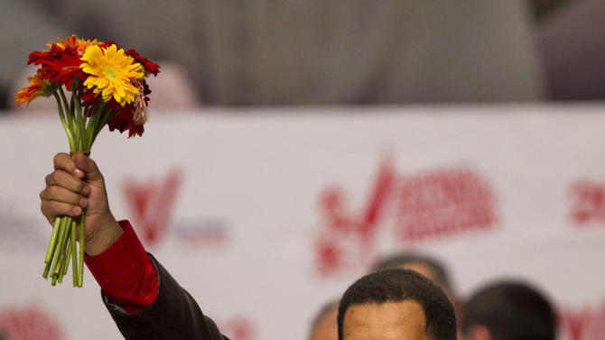 Venezuela's President Hugo Chavez holds up a bouquet of flowers during an event at Teresa Carreno theater in Caracas, Venezuela, Thursday March 29, 2012. Chavez appeared on state television early Thursday after returning home from a five-day round of radiation therapy in Cuba, where he has been undergoing cancer treatment. (AP Photo/Ariana Cubillos)