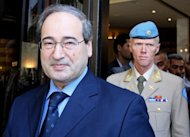Syria&#39;s Deputy Foreign Minister Faisal al-Miqdad (L) leaves with UN observer mission chief in Syria, Major General Robert Mood, following a meeting in Damascus