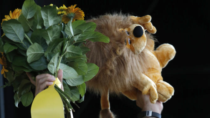 Fabian Cancellara of Switzerland, wearing the overall leader's yellow jersey, celebrates on the podium of the first stage of the Tour de France cycling race over 198 kilometers (123 miles) with start in Liege and finish in Seraing, Belgium, Sunday July 1, 2012. (AP Photo/Laurent Rebours)