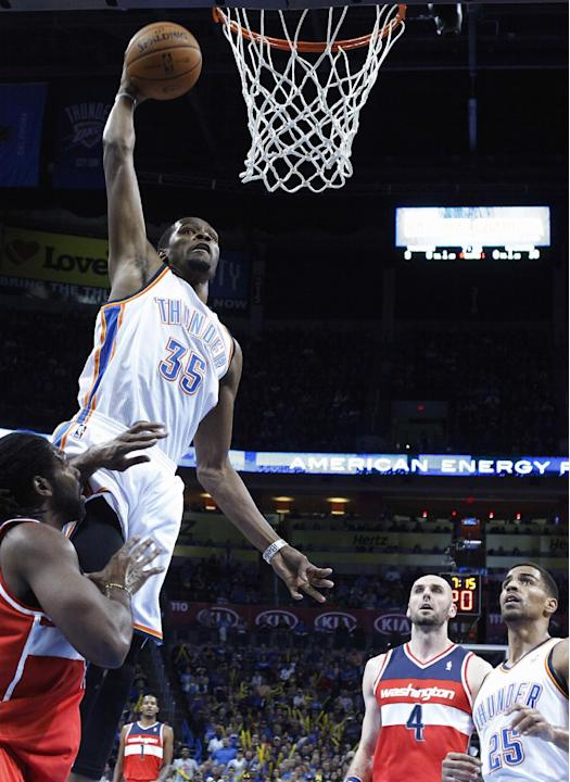 Oklahoma City Thunder forward Kevin Durant (35) goes up for a dunk in front of Washington Wizards forward Nene, left, and center Marcin Gortat (4) in the first quarter of an NBA basketball game in Okl