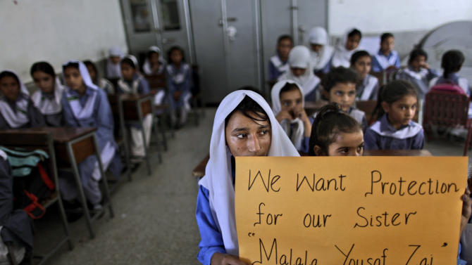 """Pakistani girls display a poster while sitting at their desk, as their teacher, not shown, talks to them about 14-year-old schoolgirl Malala Yousufzai, who was shot on Tuesday by a Taliban gunman for her role in promoting girls' education in the Swat Valley where she lives, in a school in Islamabad, Pakistan, Friday, Oct. 12, 2012. A Pakistani military spokesman says Yousufzai is in """"satisfactory"""" condition but cautions that the next few days will be critical. (AP Photo/Muhammed Muheisen)"""