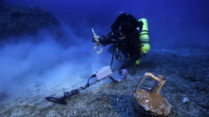 In this undated photo provided by Argo via the Greek Culture Ministry on Thursday, Oct. 9, 2014, a diver with a metal detector holds a copper ship's fitting next to a vase at the site of the Antikythera wreck off the island of Antikythera in southern Greece. The ministry said Thursday that a three-week underwater project to revisit the Roman-era wreck, first investigated more than a century ago, has completed detailed maps of the seabed and pinpointed potential metal artifacts. Divers have recovered a bronze spear that was probably part of a large statue, metal fittings from the ship and a vase. (AP Photo/ARGO via Greek Culture Ministry, Brett Seymour)