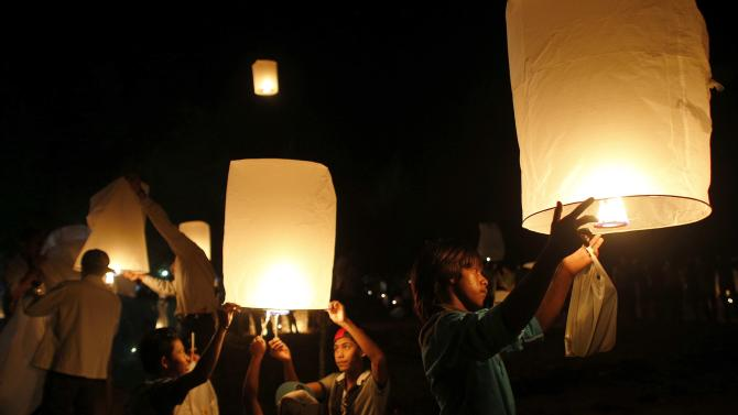 Survivors, local residents and visitors release paper lanterns during the ceremony for victims of the 2004 tsunami in Ban Nam Khem, a fishing village destroyed by the wave