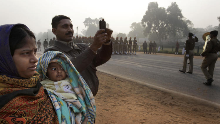 A family watches soldiers rehearse for the upcoming Republic Day parade amidst morning fog in New Delhi, India, Wednesday, Jan. 4, 2012. Dense fog enveloped many parts north India Wednesday, affecting normal life. Though India is famous for its brutally hot summers, temperatures fall sharply for a few weeks in December and January. Poor people, particularly those living on the streets, are the worst affected. (AP Photo/ Manish Swarup)