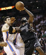 Oklahoma City Thunder's Nick Collison (4) fouls Miami Heat's LeBron James (6) during the first half of an NBA basketball game in Miami, Wednesday, April 4, 2012. (AP Photo/J Pat Carter)