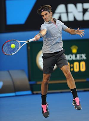 Switzerland's Roger Federer hits a forehand return to Russia's Nikolay Davydenko during their second round match at the Australian Open tennis championship in Melbourne, Australia, Thursday, Jan. 17, 2013. (AP Photo/Andrew Brownbill)