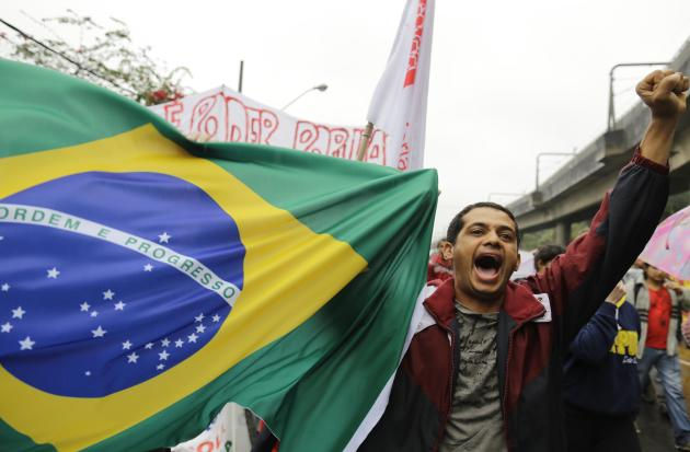 A protester shouts slogans as he helps carry a Brazilian flag in the Capao Redondo neighborhood of Sao Paulo, Brazil, Tuesday, June 25, 2013. Protesters on Tuesday returned to the streets in low-incom