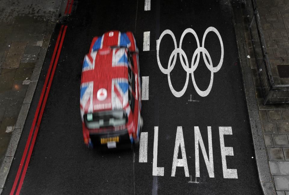 A taxi cab drives past an Olympic lane on a street as the city prepares for the 2012 Summer Olympics, central London, Monday, July 16, 2012. (AP Photo/Charlie Riedel)