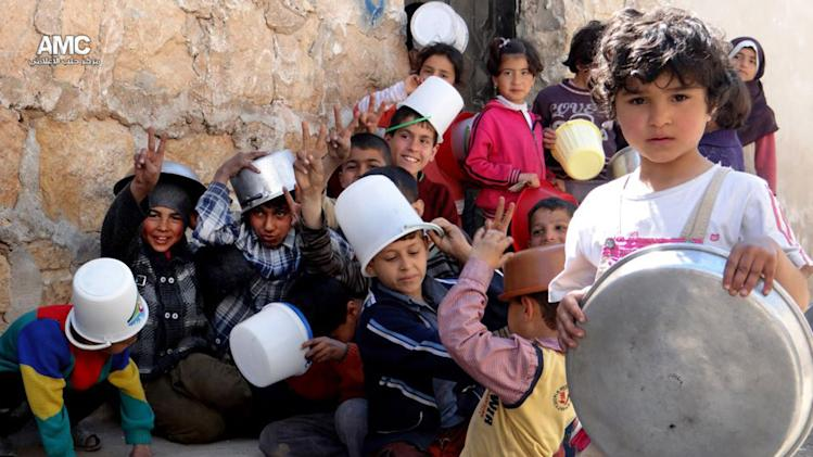 In this Monday March 25, 2013, citizen journalism image provided by Aleppo Media Center AMC which has been authenticated based on its contents and other AP reporting, Syrian children hold their pots, as they wait for food, in Aleppo, Syria. (AP Photo/Aleppo Media Center, AMC)