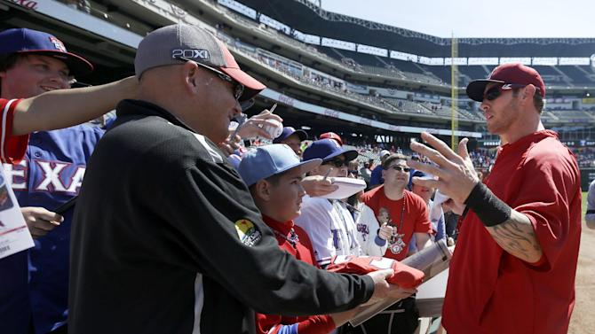 Los Angeles Angels' Josh Hamilton, right, engages fans just before signing autographs before a baseball game against the Texas Rangers Friday, April 5, 2013, in Arlington, Texas. (AP Photo/Tony Gutierrez)