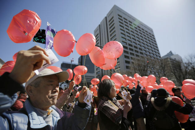 Anti-nuclear protesters prepare to release balloons during a rally in front of the Ministry of Economy, Trade and Industry (METI) in Tokyo, Tuesday, March 11, 2014. METI governs Japan's Nuclear an