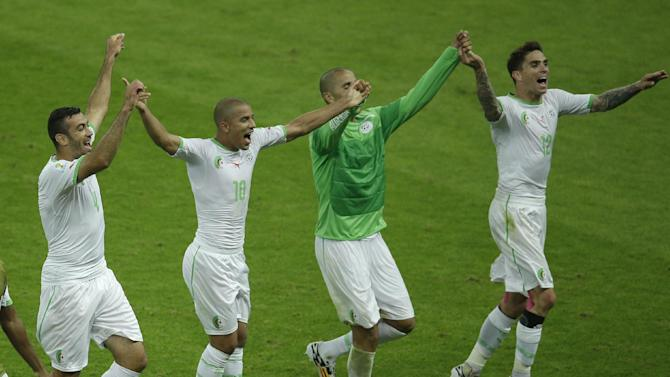 Members of the Algerian soccer team join hands as they celebrate after winning 4-2, the group H World Cup soccer match between South Korea and Algeria at the Estadio Beira-Rio in Porto Alegre, Brazil, Sunday, June 22, 2014. (AP Photo/Michael Sohn)