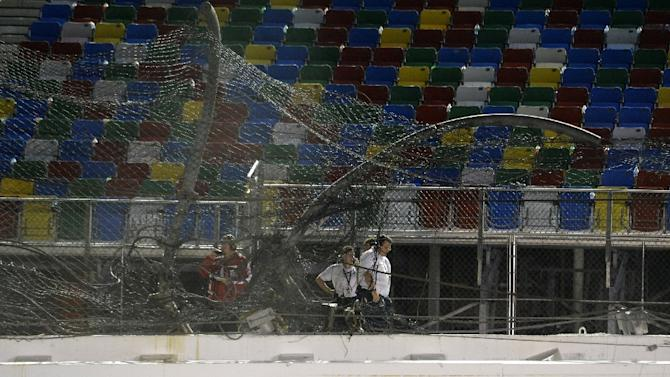 NASCAR officials and track personnel inspect damage to the catch fence after a crash at Daytona International Speedway on July 6, 2015 in Daytona Beach, Florida