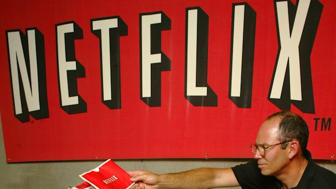 """FILE - In this July 11, 2002, file photo, Netflix co-founder Marc Randolph looks over the shoulder of Natalya Kontorovich at Netflix Inc.'s Denver distribution site. A new book,""""Netflixed: The Epic Battle for America's Eyeballs,"""" is set to go on sale Thursday, Oct. 11, 2012. The book tries to debunk a widely told tale about the company's origins and paints a polarizing portrait of its star CEO Reed Hastings. (AP Photo/Netflix, Jack Dempsey)"""