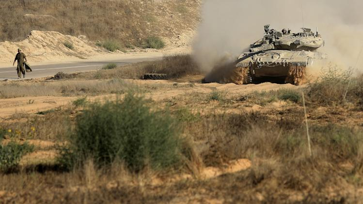 An Israeli tank advances in a staging area near the Israel Gaza border, Thursday, July 31, 2014. An Israeli defense official says the 16,000 additional reservists who are being called up will provide relief for troops who are currently fighting in Gaza. But Israeli officials have said they don't rule out expanding the Gaza operation in the coming days. (AP Photo/Tsafrir Abayov)