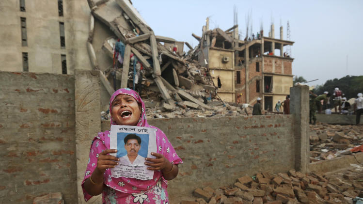 A Bangladeshi woman weeps as she holds a picture of her and her missing husband as she waits at the site of a building that collapsed Wednesday in Savar, near Dhaka, Bangladesh, Friday, April 26, 2013. The death toll reached hundreds of people as rescuers continued to search for injured and missing, after a huge section of an eight-story building that housed several garment factories splintered into a pile of concrete.(AP Photo/Kevin Frayer)
