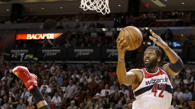 Washington Wizards forward Nene (42) shoots as Miami Heat center Hassan Whiteside (21) goes to the floor in the second half of an NBA basketball game, Friday, Dec. 19, 2014, in Miami. Washington won the game 105-103. (AP Photo/Joe Skipper)