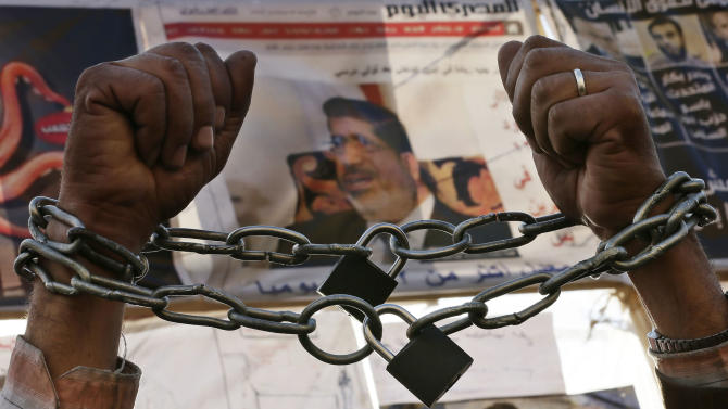 A protester chains his hands during a protest in Tahrir Square in Cairo, Egypt, Monday, Dec. 17, 2012. Egypt's political crisis shows no signs of abating as the opposition to the country's Islamist government levels new challenges against the legitimacy of a referendum on a draft constitution. Morsi also confronts criticism from the judiciary, as prosecutors hold a sit-in to demand removal of a new prosecutor general he appointed. (AP Photo/Hassan Ammar)