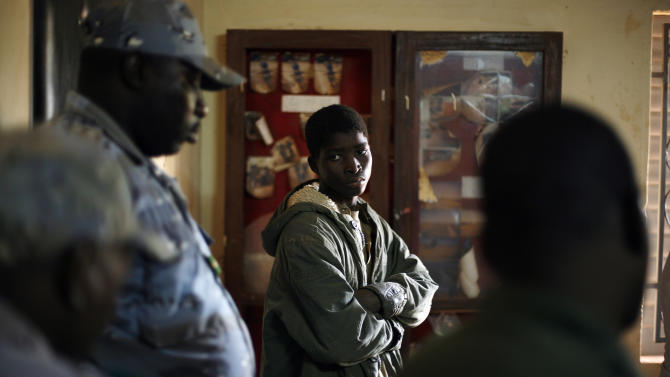 Adama Drabo, 16, stands in the police station in  Sevare, some 620 kilometers (385 miles) north of Mali's capital Bamako, Friday, Jan. 25, 2013.  Drabo, who said he was captured traveling without papers by Malian troops and eventually handed over to Gendarmes in Sevare, was arrested on suspicion of working for Islamic militant group MUJAO and caught trying to flee south, police said. A farmer's son from Niono, he admitted to having worked in the kitchens of a jihadist training base in Douentza for the past month. Drabo said his only motivation in joining the Islamic militant group had been to earn a wage, having struggled to find work at home, and that he was one of the youngest recruits on the base. (AP Photo/Jerome Delay)