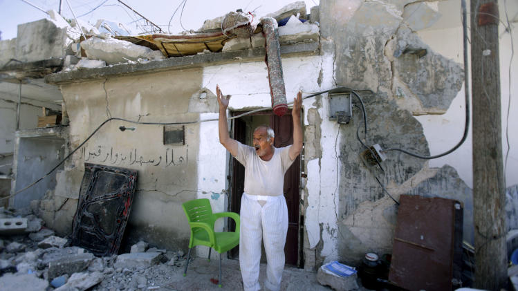 A Syrian man standing in front of his house which was destroyed from Syrian government forces shelling, reacts as a group of rebel fighters, not pictured, check the area, in Azaz, on the outskirts of Aleppo, Syria, Tuesday, Aug. 28, 2012. (AP Photo/Muhammed Muheisen)