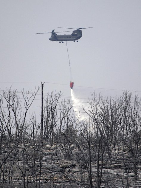 A helicopter drops water on a hotspot in a area overrun my a wildfire at Possum Kingdom Lake, Texas, Wednesday, Aug. 31, 2011. The wildfire that swept through the neighborhood on Tuesday, one of sever