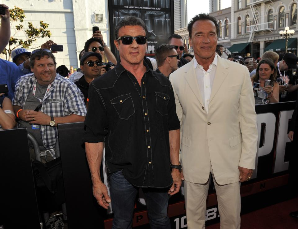"Sylvester Stallone, left, and Arnold Schwarzenegger arrive at the ""Escape Plan"" special screening on Day 2 of Comic-Con International on Thursday, July 18, 2013 in San Diego, Calif. (Photo by Chris Pizzello/Invision/AP)"