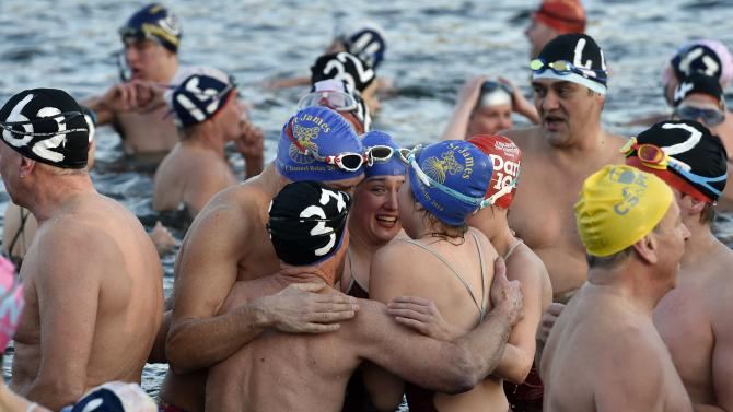 Competitors react after taking part in the Peter Pan Cup open water swim in the Serpentine Lake at Hyde Park in London