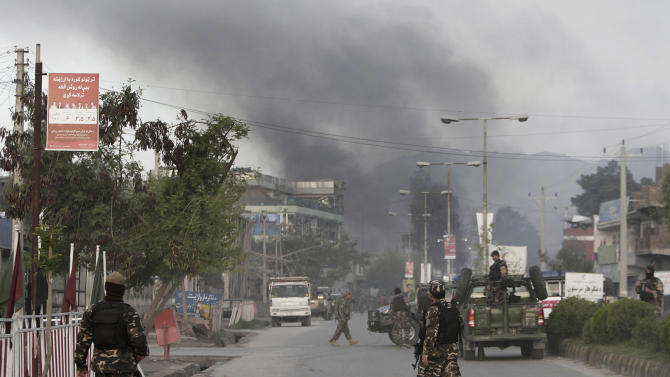 Smoke billows skyward after eight suicide bombers attacked a police headquarters in the eastern Afghan city of Jalalabad, Afghanistan, Tuesday, March 26, 2013, killing five police officers and wounding four others, a security official said. An insurgent in a bomb-laden car detonated his vehicle in front of the Jalalabad Police Quick Reaction Force to start the attack, and another seven attackers wearing bomb vests then stormed the compound. (AP Photo/Rahmat Gul)