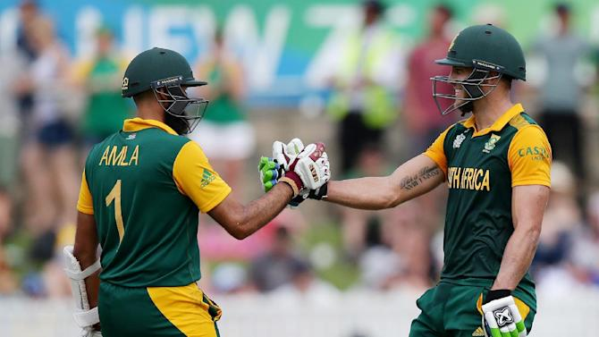 South Africa's Francois Du Plessis, right, is congratulated by teammate Hashim Amla after scoring a century during their Cricket World Cup Pool B match against Ireland in Canberra, Australia, Tuesday, March 3, 2015. (AP Photo/Rob Griffith)