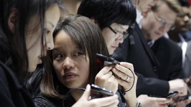 Attendees look over Samsung's new 4G LTE phone at the Consumer Electronics Show, Thursday, Jan. 6, 2011 in Las Vegas. (AP Photo/Julie Jacobson)