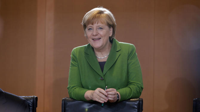 German Chancellor Angela Merkel smiles as she arrives for the weekly cabinet meeting at the chancellery in Berlin, Germany, Wednesday, Nov. 28, 2012. (AP Photo/Michael Sohn)