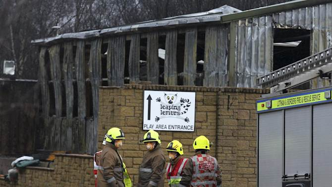 Firefighters view the damage to the reptile house at the Five Sisters Zoo in Polbeth, Scotland, Sunday April 14, 2013.  Around 50 firefighters have been tackling an early morning blaze at the zoo. (AP Photo / Andrew Milligan, PA) UNITED KINGDOM OUT - NO SALES - NO ARCHIVES