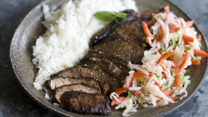 This Dec. 2, 2013 photo shows pan seared flank steak with daikon slaw in Concord, N.H. Daikon radish resemble giant white carrots, but have a mild peppery bite. (AP Photo/Matthew Mead)