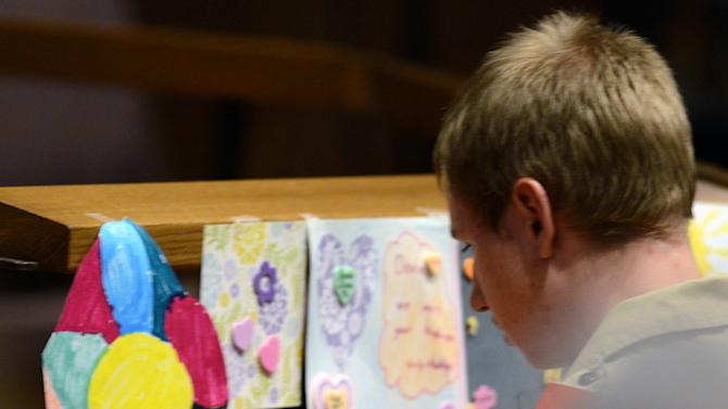 Boy Scout and Oakdale, Minn., resident Andrew Horwath, 16, hangs a photograph of nine year-old Devin Aryal at a candlelight vigil for the slain child at Holy Cross Lutheran Church in Oakdale, Tuesday night, Feb.12, 2013.  (AP Photo/Pioneer Press, Chris Polydoroff)