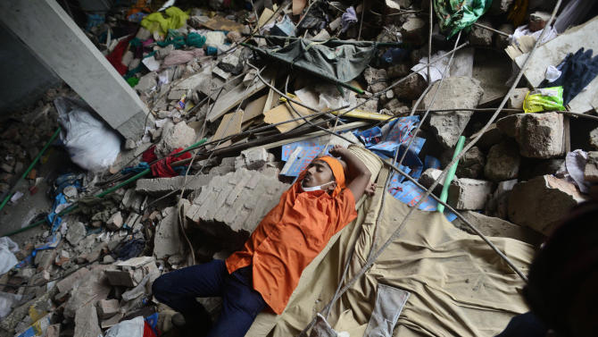 A Bangladeshi man rests on a pile of debris of a garment factory that collapsed in Savar near Dhaka, Bangladesh, Friday, May 10, 2013. The death toll from a garment factory building that collapsed more than two weeks ago near the Bangladeshi capital soared past 1,000 on Friday, with no end in sight to the stream of bodies being pulled from the wreckage of the worst-ever garment industry disaster. (AP Photo/Ismail Ferdous)
