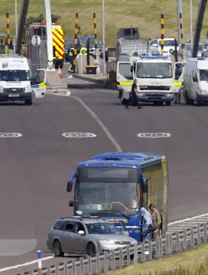 A bus stands near motorway barriers at the scene on the M6 toll motorway, near Weeford toll plaza in the West Midlands, around 116 miles (187 kilometers) north of London, after the motorway was closed following a police-led incident Thursday July 5, 2012. Armed police closed a section of the M6 highway in both directions Thursday during a police-led incident involving a bus in central England.  (AP Photo/Dave Thompson/PA Wire) UNITED KINGDOM OUT