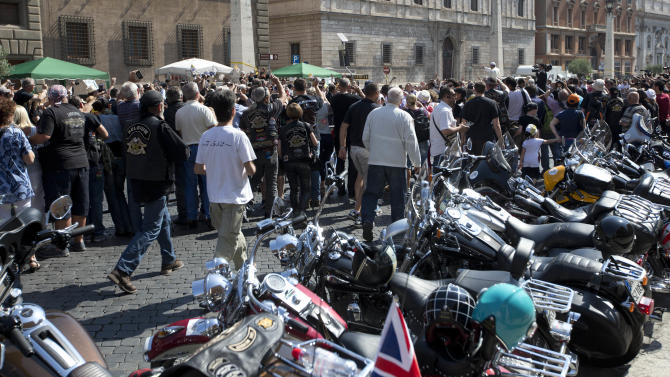 Harley Davidson motorcycles are parked as Pope Francis, white figure seen above the crowd at top right, arrives to celebrate mass in St. Peter's Square, at the Vatican, Sunday, June 16, 2013. Thousands of Harley-Davidson lovers have met in Rome to celebrate the motorcycle company's 110th anniversary. The four-day event includes a major parade through the heart of the city and a blessing by Pope Francis during his Angelus noon prayer at the Vatican on Sunday.  (AP Photo/Andrew Medichini)