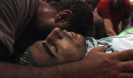 A Palestinian mourner touches the body of Ibrahim Sarhan, killed by Israeli military action, during his funeral in the West Bank refugee camp of El Fara, north of Nablus, Wednesday, July 13, 2011. Sarhan was killed Wednesday in an Israeli military raid on a West Bank refugee camp, Palestinians said, when Israeli troops had entered the El Fara camp in pursuit of a fugitive militant. According to witnesses residents began throwing stones at the troops, who responded with live fire, killing Sarhan. (AP Photo/Mohammed Ballas)