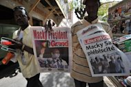 A street vendor sells Senegalese newspapers in Dakar. Senegal&#39;s Macky Sall on Monday hailed a new era after triumphing over veteran leader Abdoulaye Wade in a presidential poll lauded the world over as an example for African democracy