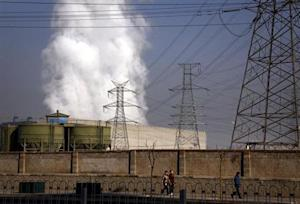 Pedestrians walk along a footpath in front of a massive chimney billowing smoke for a coal-burning power station in central Beijing January 12, 2012. REUTERS/David Gray/Files