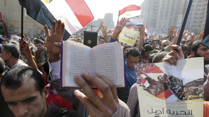 Supporters of the Muslim Brotherhood and ousted Egyptian President Mohamed Mursi shout slogans against he military and interior ministry and rise copies of the Koran t, during a protest in the Cairo suburb of Matariya