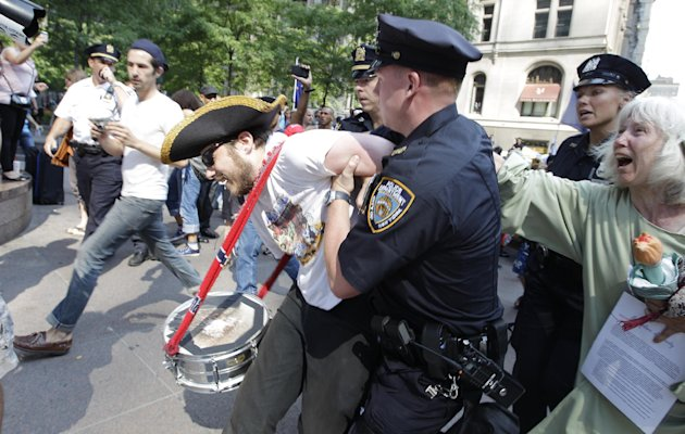 An Occupy Wall Street protestor is arrested in Zuccotti Park Wednesday, July 11, 2012, in New York. Occupy marchers with guitars are marking the 100th birthday of the late folk singer-songwriter Woody